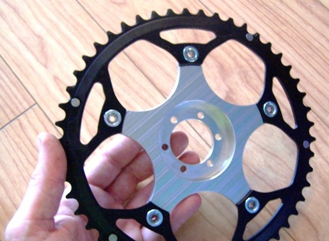 Here's an aluminum spider from Matt/recumpense that attaches a common chainring to the disc-brake flange on the left side of a rear wheel.