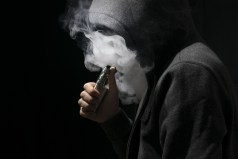 Isolated young man on a black background holding an electronic cigarette, vaping device, mod, e-cig.