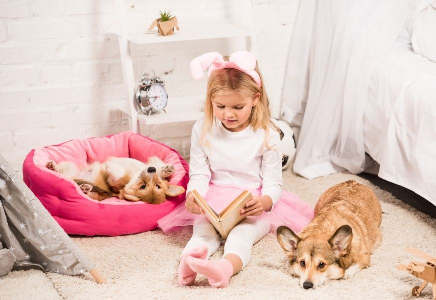 girl reading to dogs in bedroom