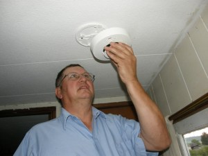 An ESC fire tech replaces a smoke detector.
