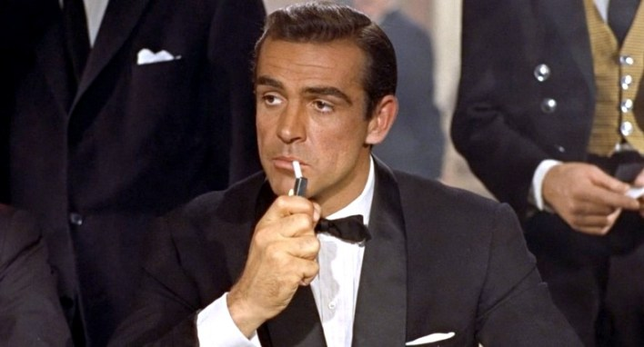 Sean Connery in Dr. No brings a shawl collar  midnight blue tuxedo with midnight satin silk trimmings and satin silk bow tie.