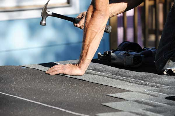 Roofer hammering shingles on concord roof installation
