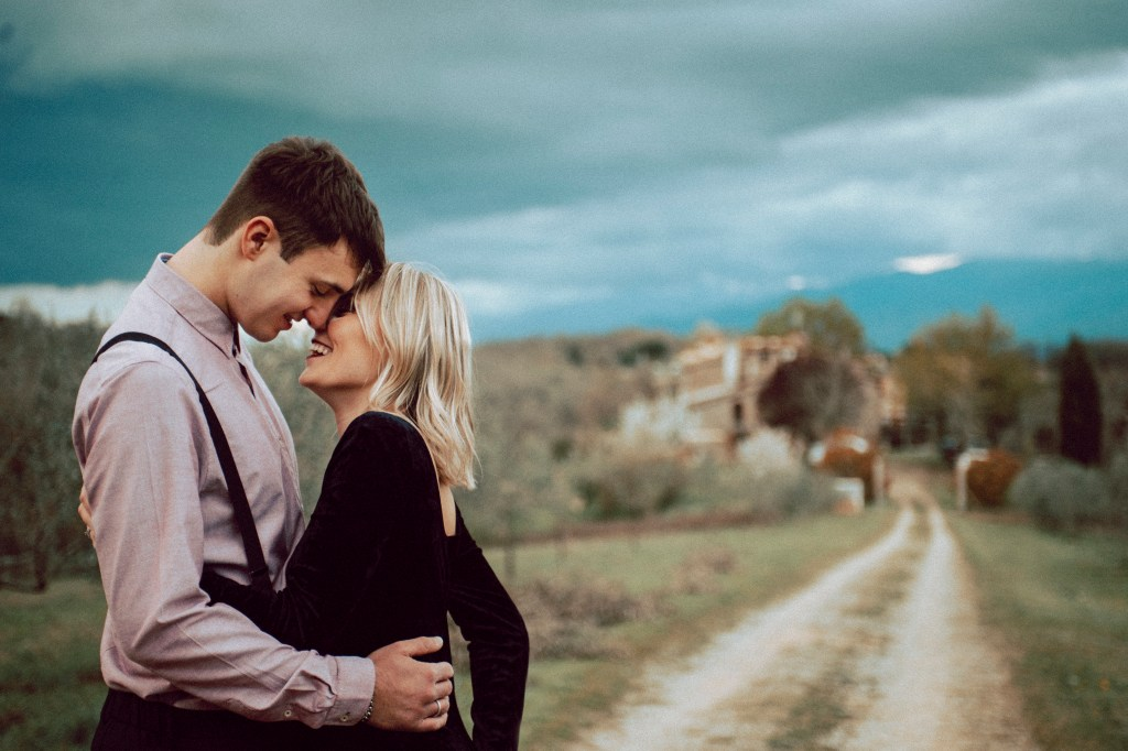 Tuscany Engagement Session - Couple hugging with Tuscany countryside in the background