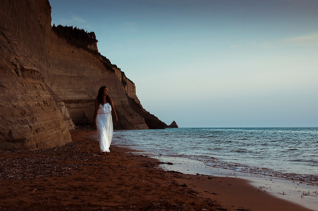 Greece Destination Engagement - Corfu - beautiful back-haired girl dressed in white walking on the beach
