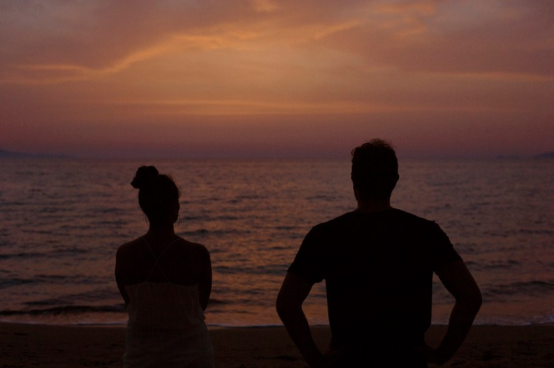 Greece Destination Engagement - Corfu - Silhouette of two lovers looking at the horizon by the shore