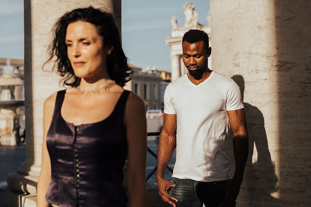 Interracial couple chasing among columns of Saint Peter's square