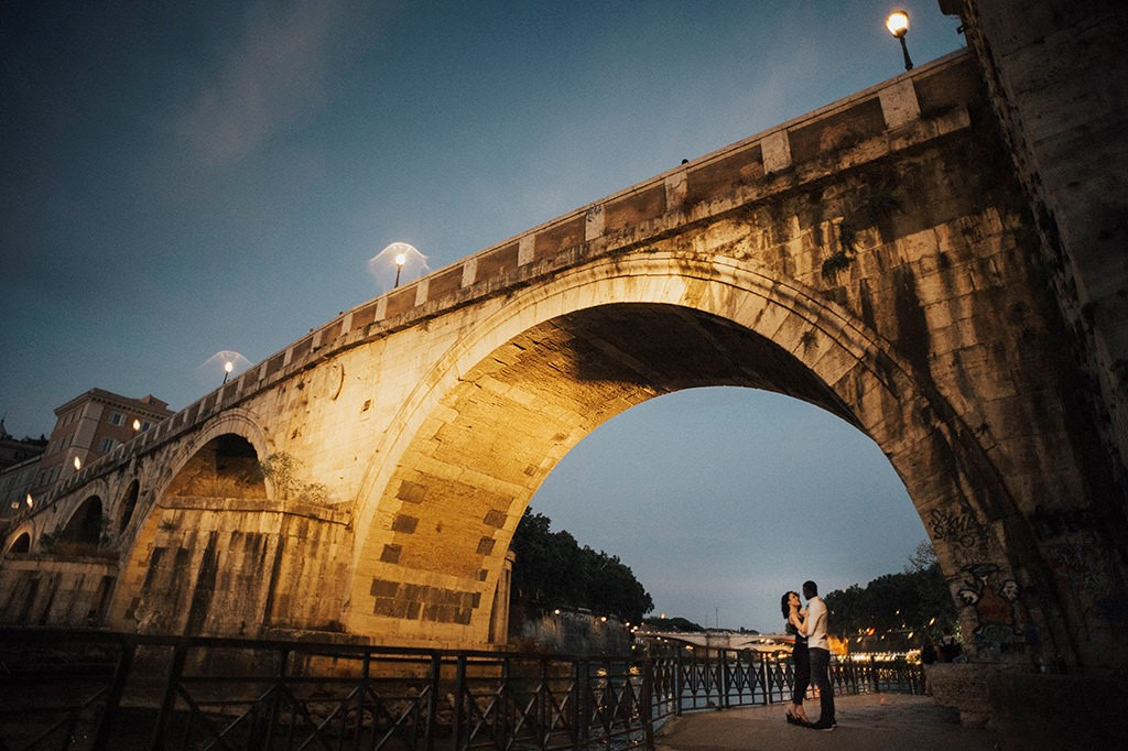 Interracial couple hugging under the bridge in Trastevere