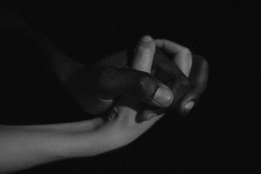 Interracial couple - detail - interlaced hands