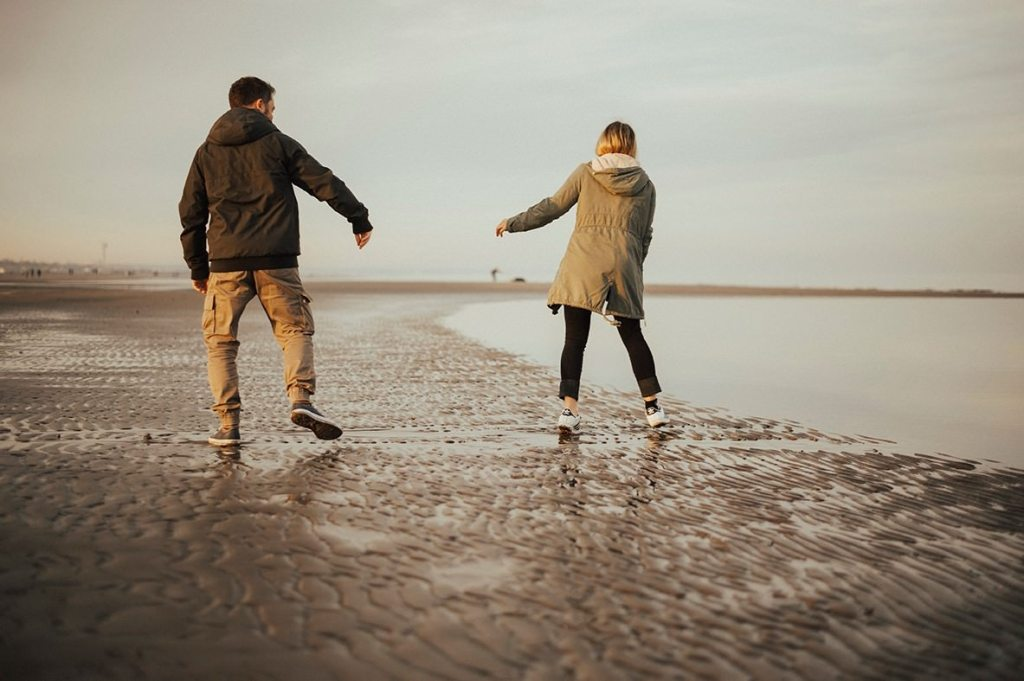 couple walking and dancing on the shore