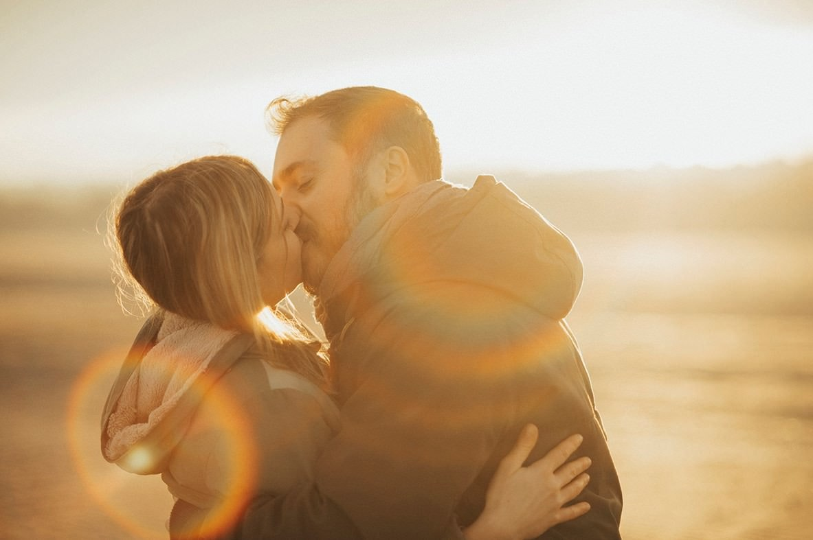 Sweet couple kissing on a beach with rainbow flare effects