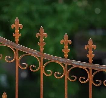 Verzierungen eines geschwungenen Tors in Edelrost mit Spitze Lilie