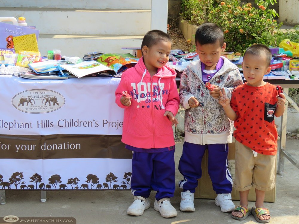 Kids trying out their new clothes and toy cars donated by Elephant Hills' guests