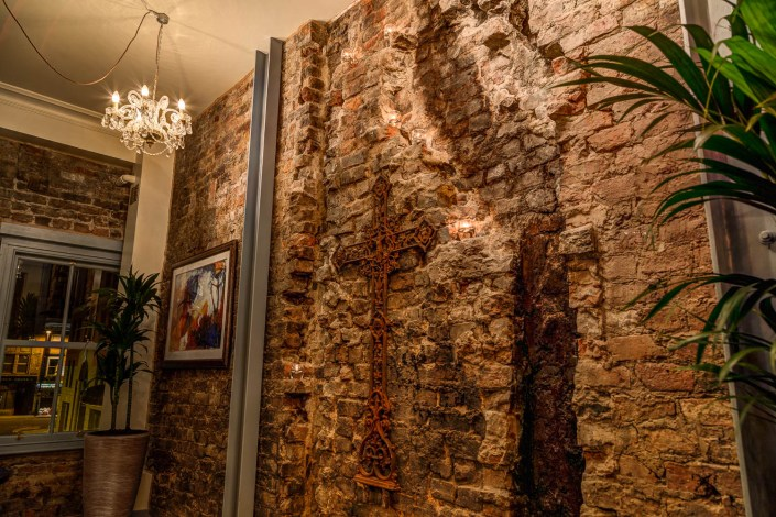 Exposed brickwork and salvaged cross at El Gato Negro Manchester