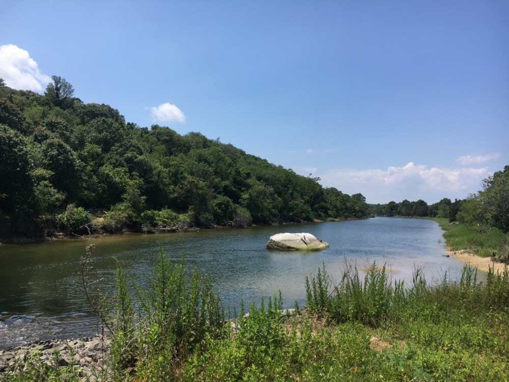 A large rock in the middle of the creek on a beautiful summer day at Sunken Meadow State Park in Kings Park, Long Island, NY.