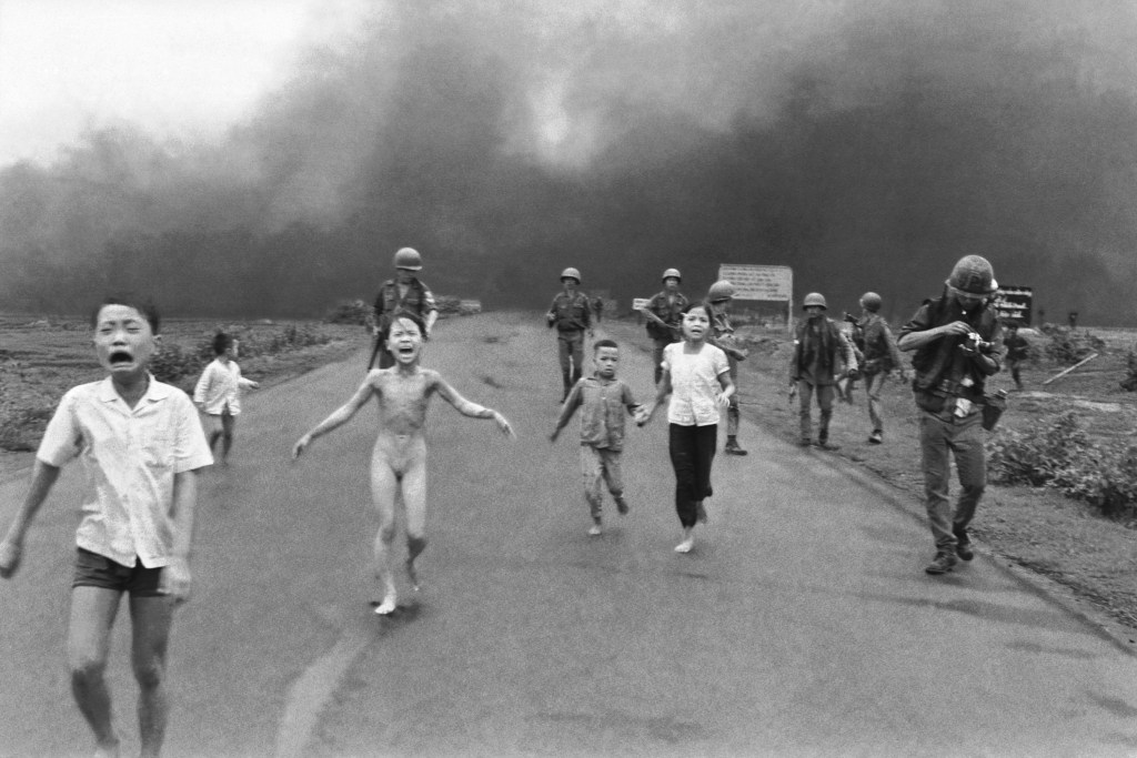 South Vietnamese forces follow after terrified children, including 9-year-old Kim Phuc, center, as they run down Route 1 near Trang Bang after an aerial napalm attack on suspected Viet Cong hiding places, June 8, 1972. A South Vietnamese plane accidentally dropped its flaming napalm on South Vietnamese troops and civilians. The terrified girl had ripped off her burning clothes while fleeing. The children from left to right are: Phan Thanh Tam, younger brother of Kim Phuc, who lost an eye, Phan Thanh Phouc, youngest brother of Kim Phuc, Kim Phuc, and Kim's cousins Ho Van Bon, and Ho Thi Ting. Behind them are soldiers of the Vietnam Army 25th Division.