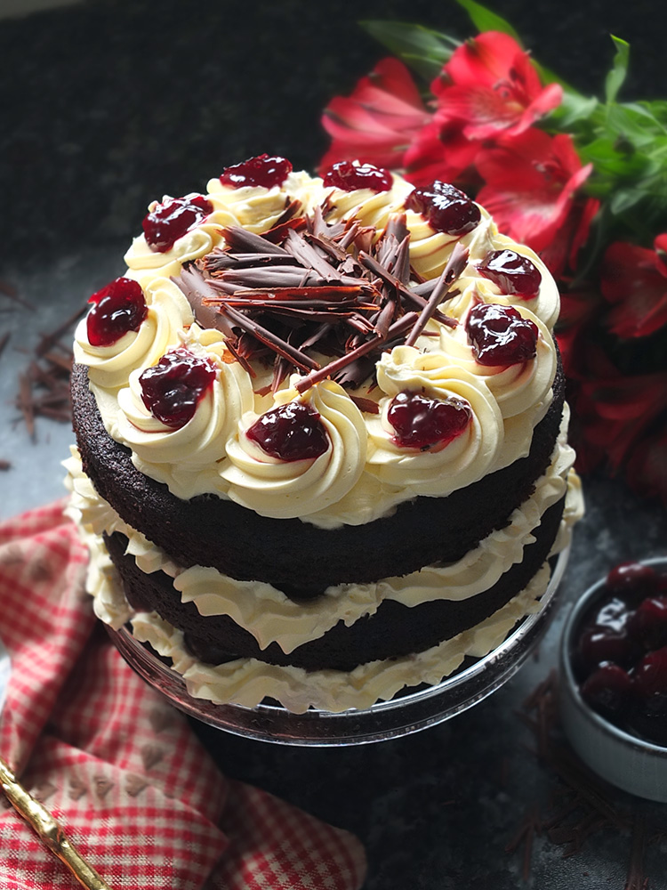 Layers of rich chocolate cake drizzled with cherry brandy sandwiched together with sweetened whipped cream and black cherry conserve. The cake is finished with more cream and some dark chocolate curls. #chocolate #chocolatecake #blackforestcake #baking