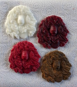 Irish water spaniel head ornaments in white, dark red, blackened, and bright red beeswax.