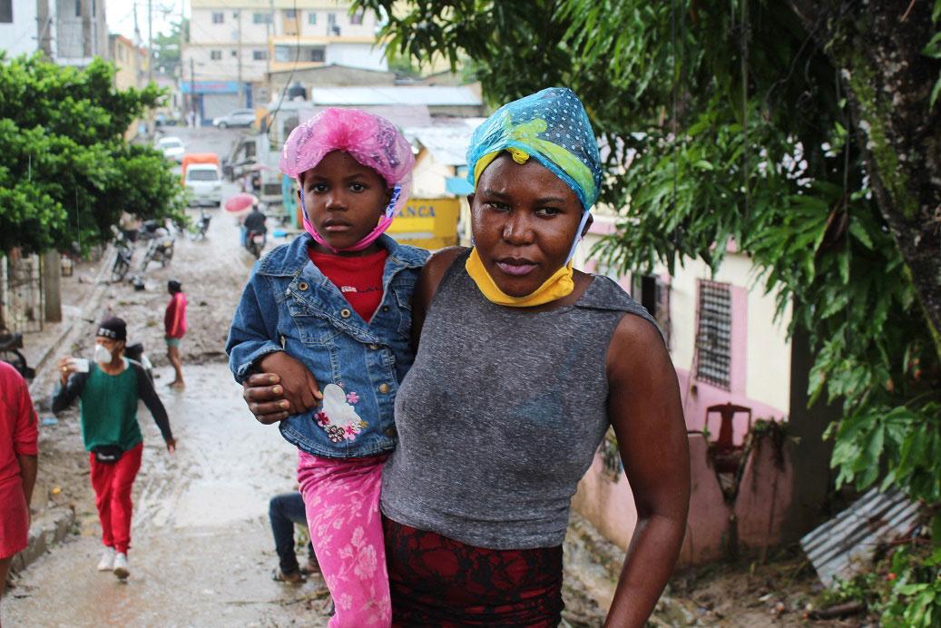 Esta mujer de origen haitiana con su hijo en los brazos sale a ver donde puede ir a vivir pues perdió todos