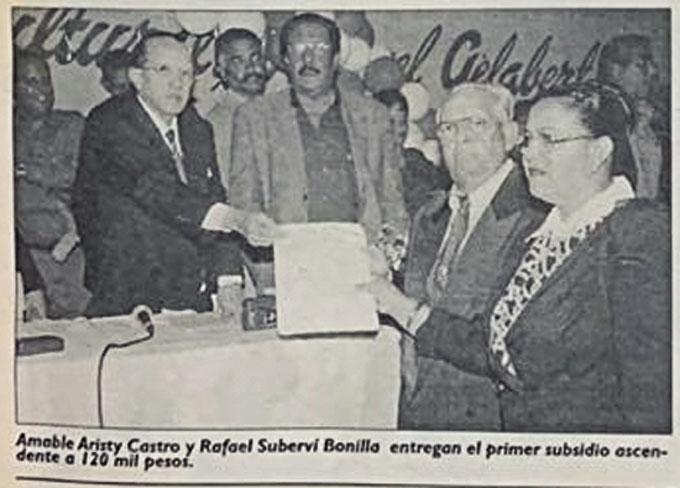 ❏ La foto histórica en la que Amble Aristy Castro y Fello Suberví entregan un cheque por 120 mil pesos que significó el primer ingreso del Distrito Municipal. Foto Joseph Suriel.