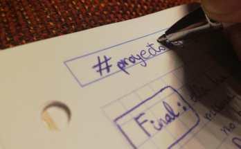 """Mano escribiendo en una libreta donde se lee """"#proyecto""""."""