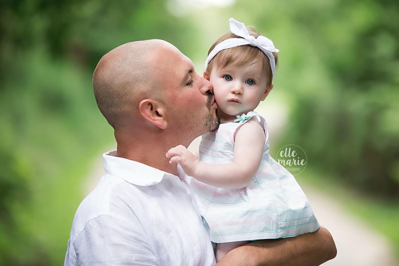 dad kissing baby daughter