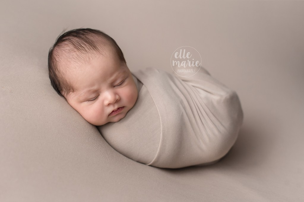 newborn wrapped in beige