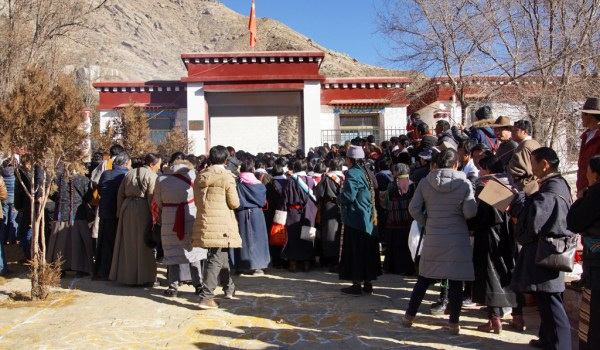 Special ceremony at Sera Monastery, Lhasa: Tibetans waiting to for the residential building of who had passed the highest exams, to get in and pay their respects