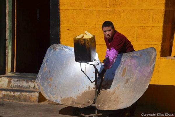 A nun is melting yak butter using solar power