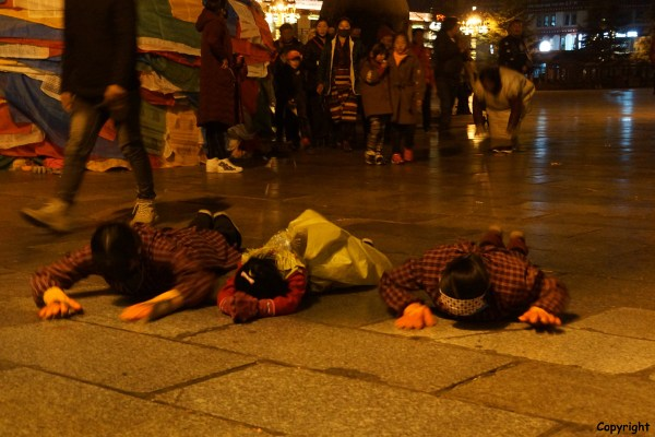 Lhasa, children prostrating around the Jokhang Temple