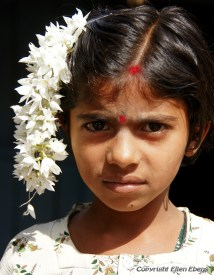 Girl with flowers in her hair in a little village