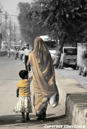 Woman with her daughter walking on a busy road, Satna