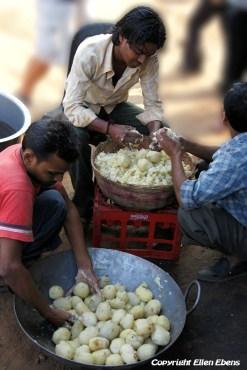 Young men at a street restaurant preparing food
