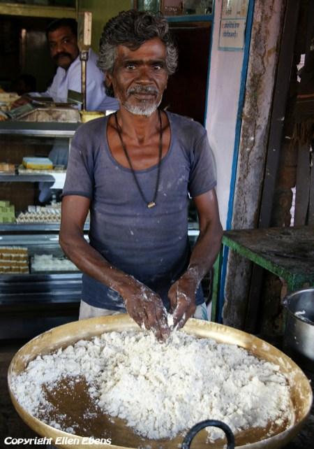 A man at a street restaurant prepares food