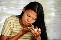 Near Mandalay, woman affixing het tanaka make up at the Kaunghmudaw Pagoda