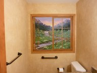 Window Mural painted on a bathroom wall. Mountainous meadow and stream on view. Mural by Ellen Leigh