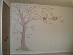 A soft Apple tree blooms with two robins carrying a ribbon with the baby's name on it over the crib. Mural by Ellen Leigh