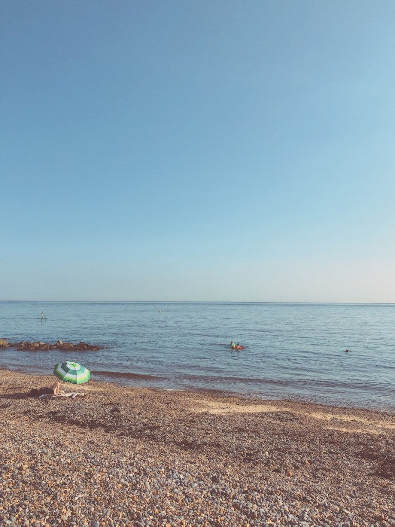 striped beach umbrella stony beach