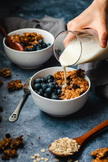 oatmeal cookie granola served in bowls with blueberries, soy milk being poured into one bowl