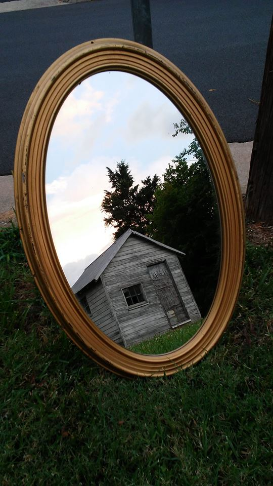 Photo of mirror reflecting a shed.