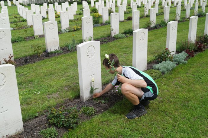 Boy lays flower at Commonwealth War Grave in Holland.