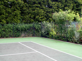 Mature planting camouflages the tennis court fence