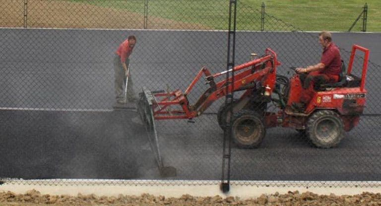 Laying the surface of a new tennis court by Elliott Courts