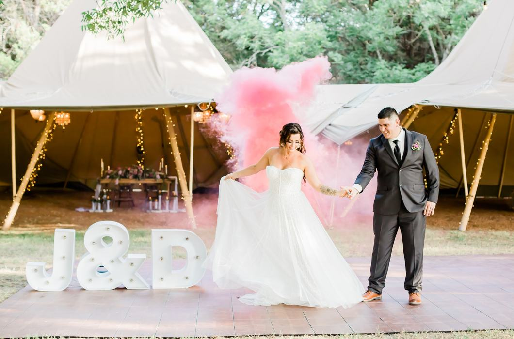 Wedding Couple on Outdoor Dance Floor Outside Tipis with Smoke Bombs