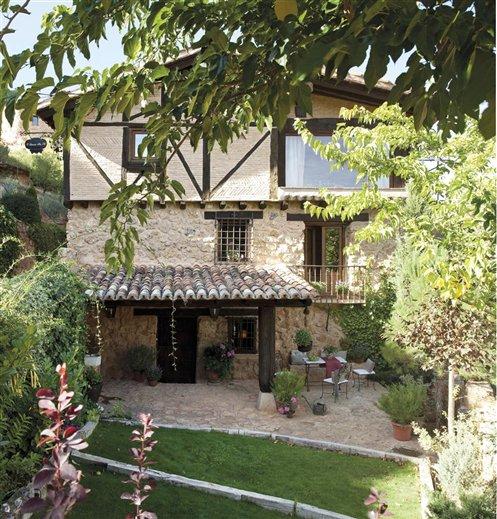 El jardn de una casa de piedra y ladrillo