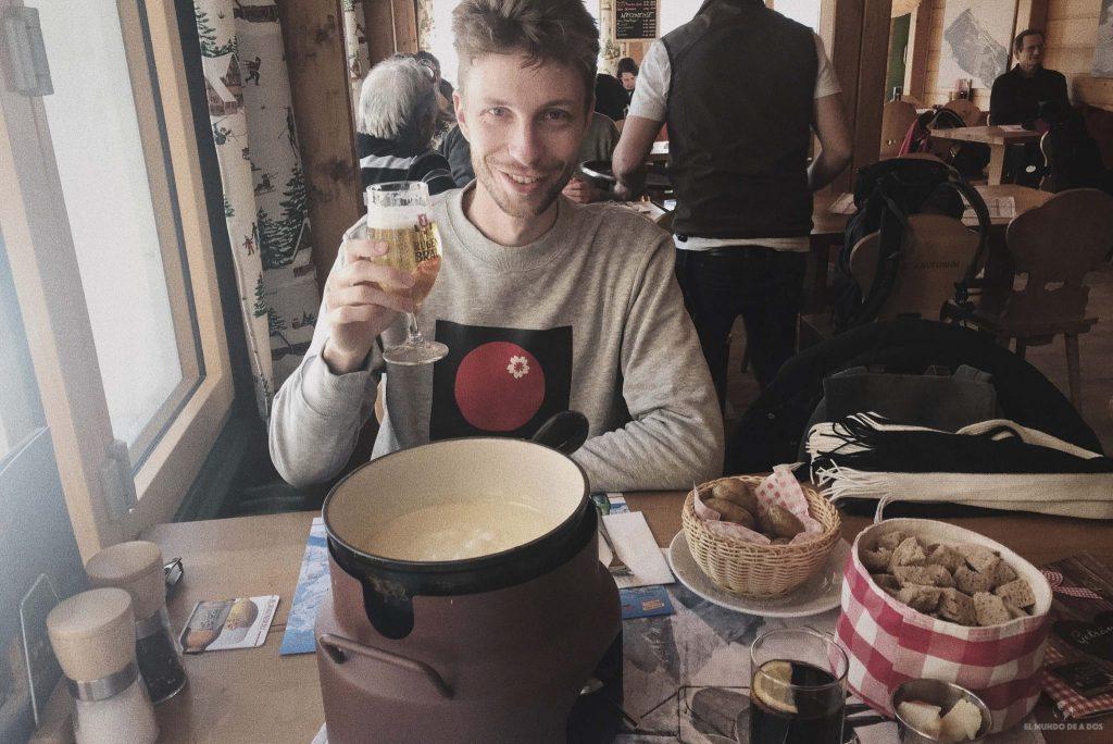 Probando una fondue de queso en Suiza en invierno