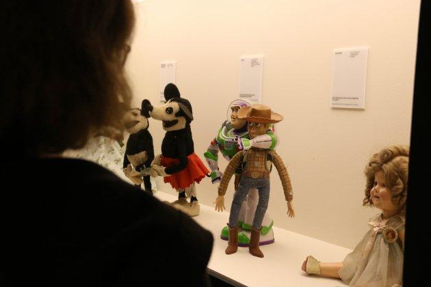 Una visitant a l'exposició 'El joc del cinema' de la Filmoteca de Catalunya observa uns ninots exposats. Mar Vila