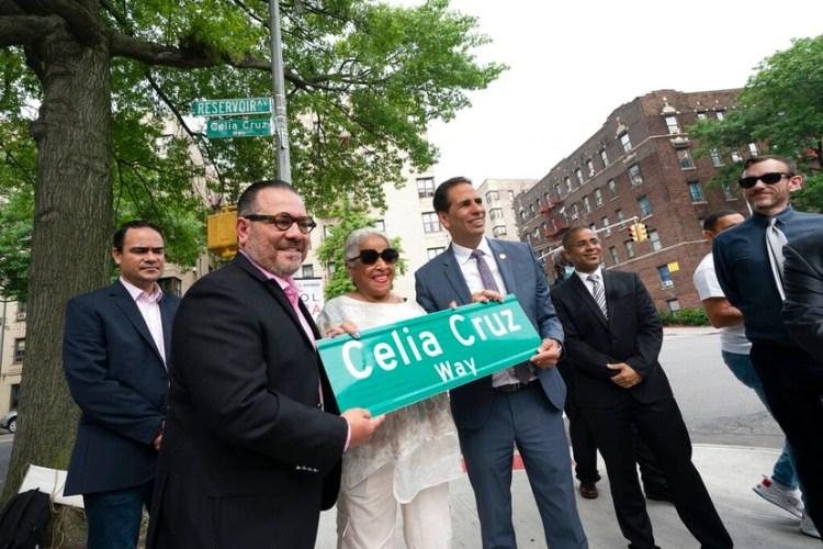 Omer Pardillo, exmanager de Celia Cruz, a la izquierda, Ruth Sánchez Laviera, quien fue amiga de la difunta cantante cubana, y el concejal de Nueva York Fernando Cabrera, a la derecha, sostienen un letrero con las palabras Celia Cruz Way.