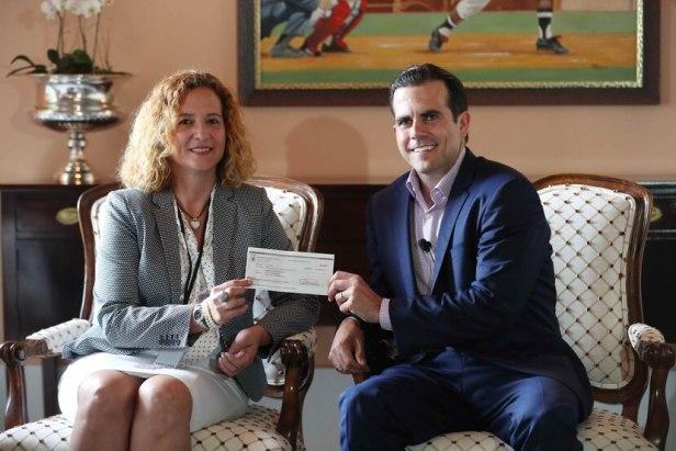 El gobernador Ricardo Rosselló y la presidenta del Copur, Sara Rosario, posan junto al cheque.