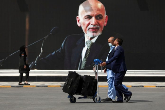 Passengers walk to a terminal at the airport in Kabul to leave Afghanistan.  In the background, a photo of President Ashraf Ghani, who left the country in the midst of the crisis with the Taliban.