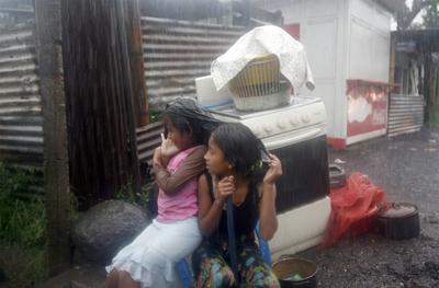 Dos niñas cubriéndose del agua en Guatemala.